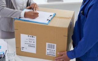 Le livreur est en train de livrer le colis express pendant que le client signe le bon de livraison